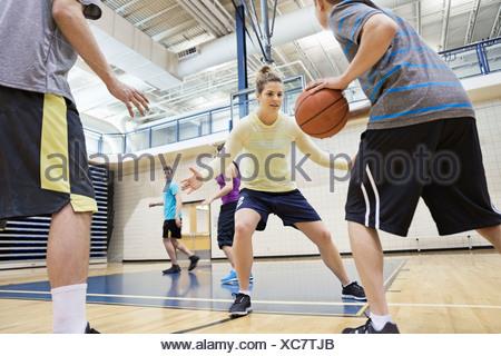 Les hommes et les femmes jouant au basket-ball en salle de sport Banque D'Images