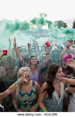 Les jeunes femmes cheering in powder foule à summer music festival Banque D'Images