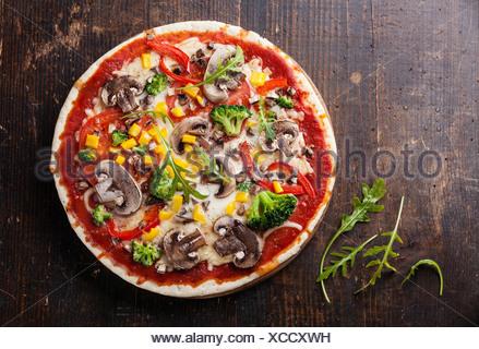 Pizza végétarienne avec champignons et ruccola sur table en bois Banque D'Images