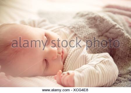 Deux mois bébé garçon endormi dans un lit bébé Banque D'Images