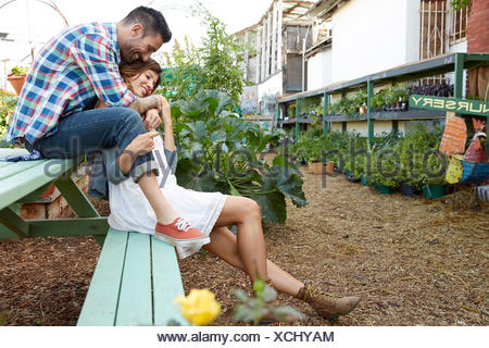 Affectionate couple sitting on bench in plant nursery Banque D'Images
