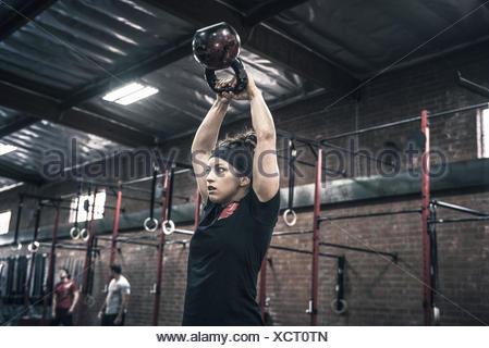 Young woman holding up électrique bells in gym Banque D'Images