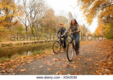 Happy young couple à vélo le long de la promenade Riverside à l'automne Banque D'Images