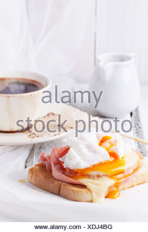 Petit-déjeuner avec une tasse de café et des toasts avec du fromage et œuf poché servi sur table en bois blanc Banque D'Images