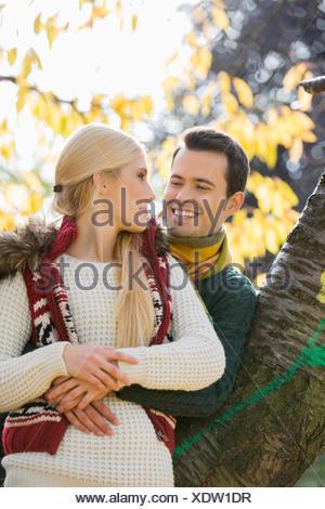 Happy young man hugging woman tout en s'appuyant sur tronc d'arbre au cours de l'automne dans le parc Banque D'Images