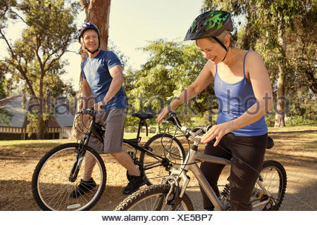 Mature couple chatting on bicycles in park Banque D'Images