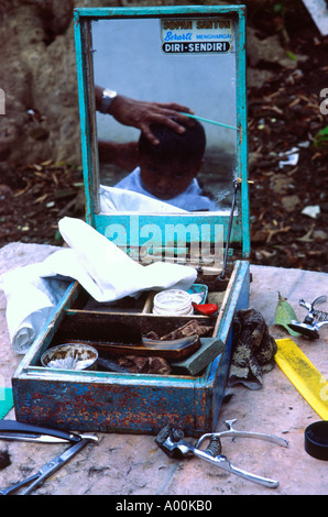 Jeune garçon avoir couper les cheveux à l'extérieur se reflète dans le miroir de la boîte à outils du brut coiffeurs Banque D'Images