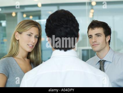 Deux associé commercial parlant à l'homme avec back to camera Banque D'Images