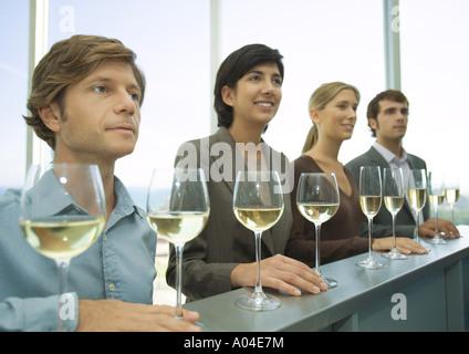Quatre adultes dans la rangée debout avec les mains de bar, verres de vin en face d'eux Banque D'Images