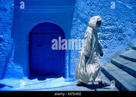 Musulman marocain dans un burnoose blanc robe jellaba jusqu'à pied des mesures contre la paroi d'argile bleu Maroc Banque D'Images