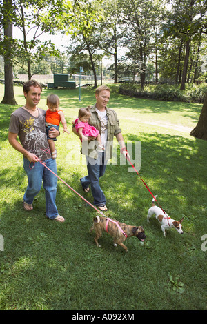 Les bébés et les pères Holding Walking Dogs Banque D'Images