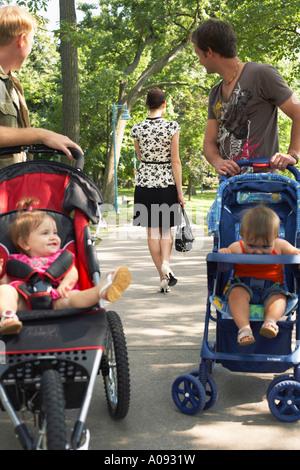 Les hommes avec des bébés en poussette à la femme à la marche loin