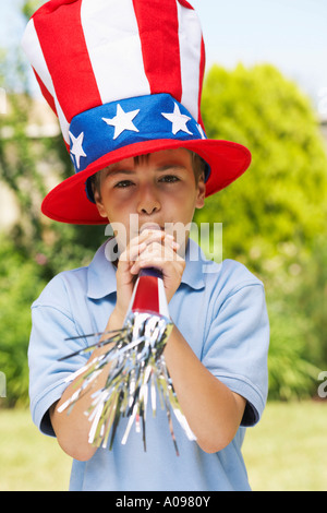 Portrait of Boy Wearing grandes Stars and Stripes Hat, soufflage crécelle Horn Banque D'Images