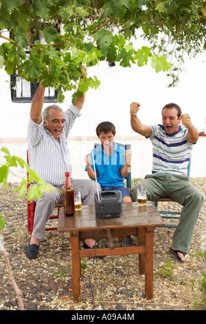 Grand-père, père et fils à regarder la télévision en arrière-cour