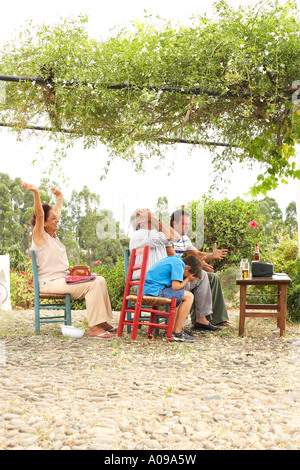 Grand-père, la grand-mère, père et fils à regarder la télévision en arrière-cour