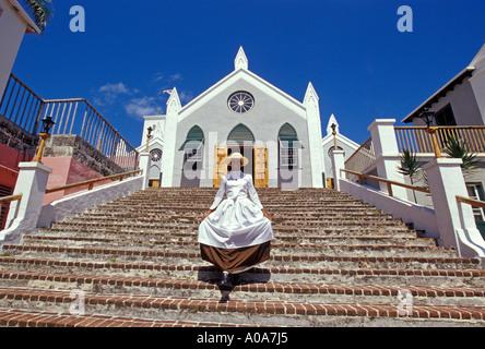 Caraïbes BERMUDES Ville de St George femme en robe période walking down steps de St James Church Banque D'Images