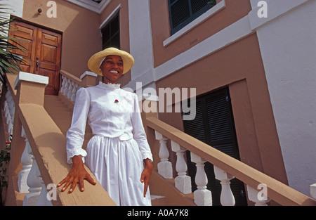 Les Bermudes Ville de Georgetown Smiling woman in dress période walking down museum étapes Banque D'Images