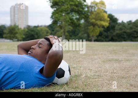 Teenage boy reposant sur le football