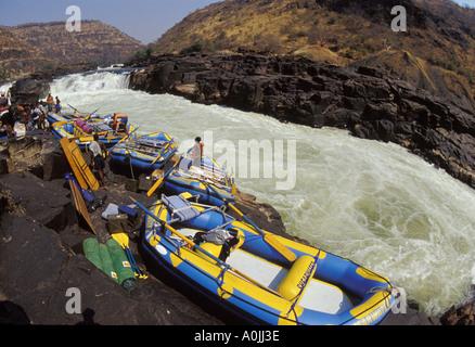 Guides de Rafting radeaux et équipements de portage ci-dessous des cascades dangereuses sur le fleuve Zambèze, l'Afrique Banque D'Images