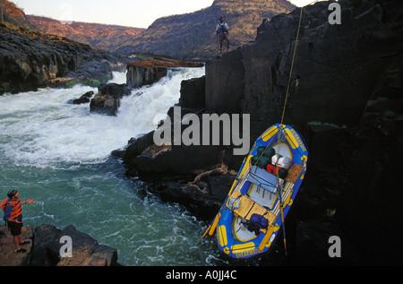 Guides de Rafting radeaux et équipements de portage ci-dessous Mowenba Falls sur la rivière Zambèze, l'Afrique Banque D'Images
