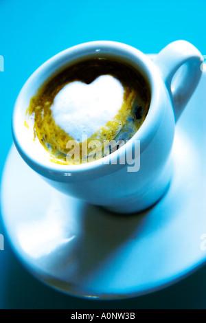 Tasse remplie de café avec de la mousse en forme de coeur