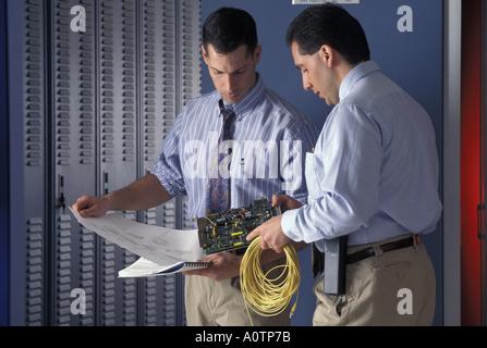 Les techniciens travaillant sur du matériel de télécommunications Banque D'Images