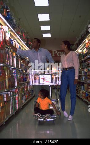 Un jeune couple à l'épicerie alors que leur fils se trouve sur la grille du bas du panier Banque D'Images