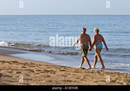 Mature couple walking sur la plage de Maui, Hawaii Banque D'Images