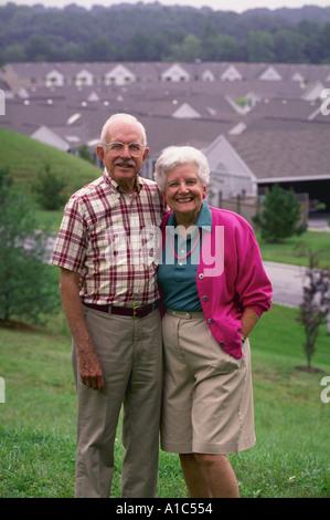 Un couple actif pose sur une colline avec vue sur leur collectivité de retraités dans le Maryland model publié Banque D'Images