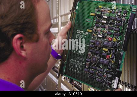 Un MCI Corporation technicien vérifie un circuit de sélection dans un nouveau commutateur téléphonique dans la région Banque D'Images