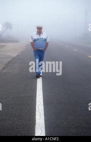 Homme marchant le long de la ligne blanche de la rue Brouillard Banque D'Images