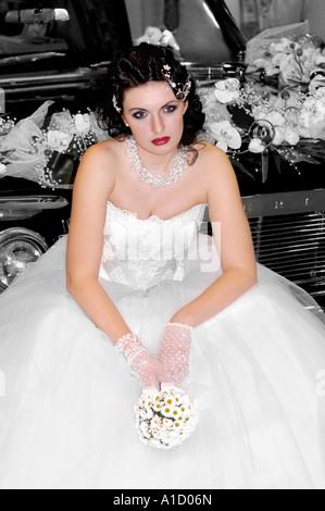 Jeune femme mariée solitaire en robe de mariage de l'emplacement sur une voiture Banque D'Images