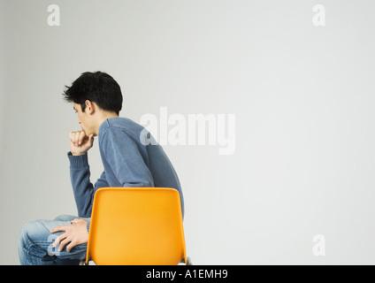 Jeune homme assis sur une chaise, tenant le menton Banque D'Images