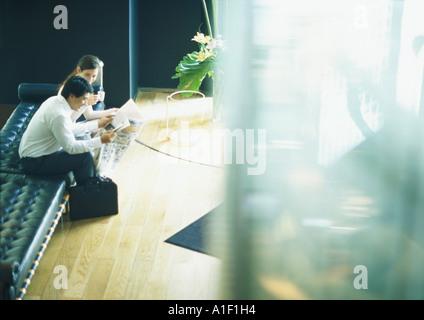 Homme et femme assis sur un banc dans le hall, high angle view Banque D'Images