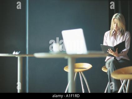 Businesswoman travaillant seul dans l'établissement cafe Banque D'Images