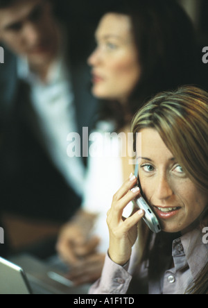 Businesswoman using cell phone in front de deux co-workers