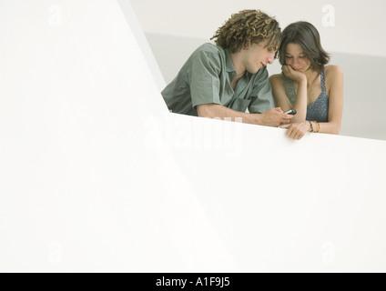 Jeune homme et femme se penchant sur le bord du balcon looking at cell phone Banque D'Images
