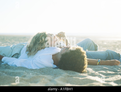 Teenage couple lying on beach Banque D'Images