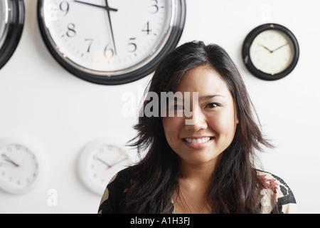 Close-up of a businesswoman smiling standing en face d'horloges sur le mur Banque D'Images