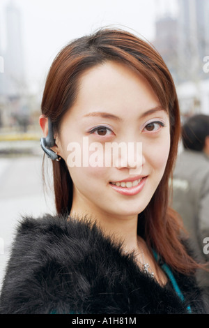 Portrait d'une jeune femme portant un dispositif mains libres Banque D'Images