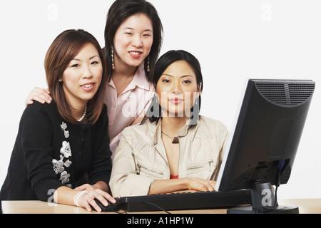 Portrait de trois businesswomen smiling in front of a computer Banque D'Images