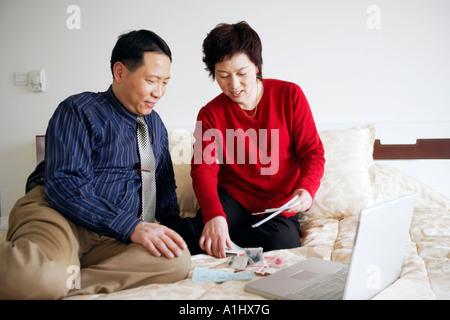 High angle view of a young couple assis sur le lit avec du papier-monnaie et d'un ordinateur portable