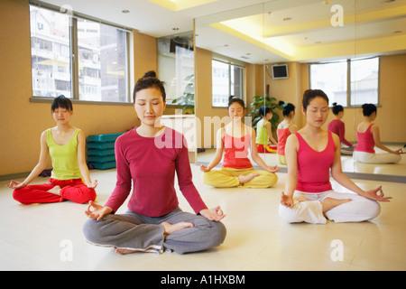 Quatre jeunes femmes assis dans la position du lotus Banque D'Images