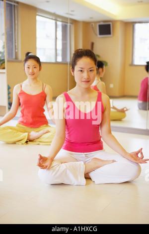 Portrait d'une jeune femme assise dans la position du lotus Banque D'Images