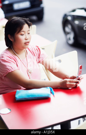 High angle view of a young woman sitting at a sidewalk cafe et holding a mobile phone