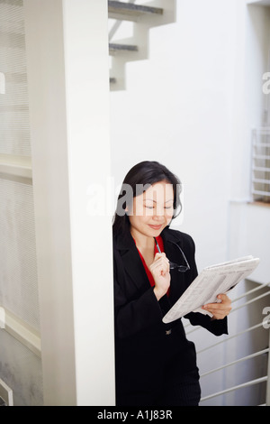 Businesswoman holding a newspaper and smiling Banque D'Images