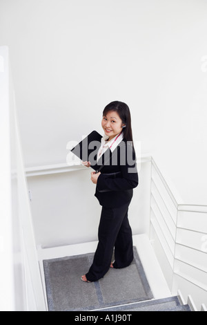 High angle view of a woman standing on the staircase and smiling