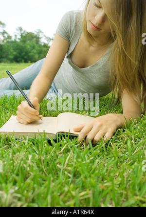 Jeune femme couchée dans l'herbe, écrit dans le journal Banque D'Images