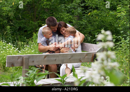 Family Sitting on Park Bench Banque D'Images