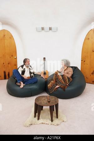 Couple assis dans des sièges-sacs dans la salle de séjour Banque D'Images